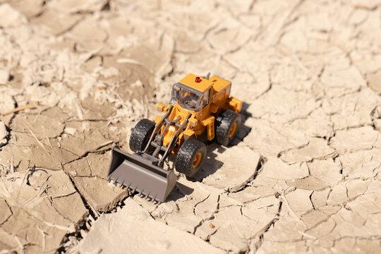 渇水でひび割れた地面とホイールローダー