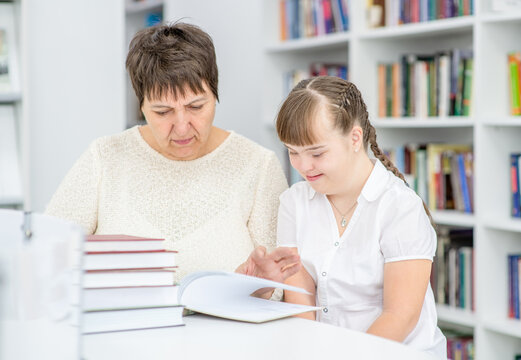 Teacher and girl with syndrome down read a book at library. Education for disabled children concept