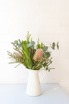 Vertical view of Australian native flower bouquet including banksia and leucadendron with eucalyptus leaves against white wall (selective focus)