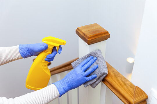 Woman hands in gloves cleaning stairs railings with rag