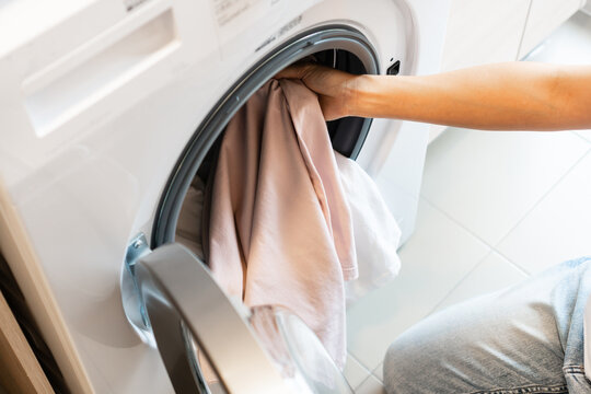 Asian woman putting clothes into washing machine in kitchen at home. Laundry concept. Top view
