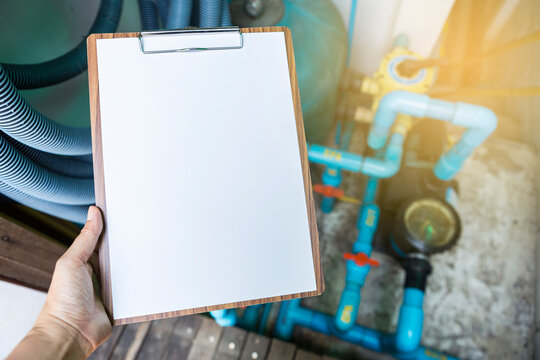 Blank A4 paper sheet on wooden clipboard over blurred swimming pool piping and filtration system, maintenance service, engineering report