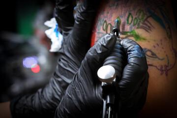 Fototapeta Female tattoo artist making tattoo on a men's arm