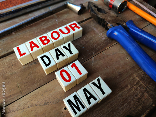 first May is celebrated as Labourers day , poster of may day celebration with tools on Wooden background.