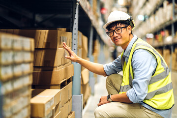 Fototapeta Portrait of smiling asian engineer man order details checking goods and supplies on shelves with goods background in warehouse.logistic and business export obraz