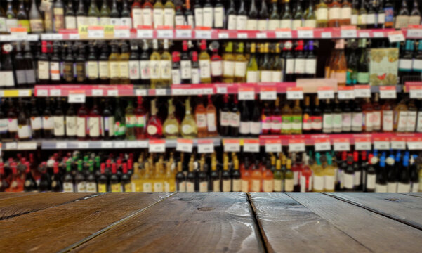 Blurred image of a liquor store with drinks. Wine bottles on the shelves. In the foreground is a table or counter.