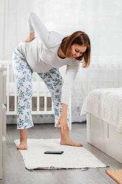 A pregnant woman can hardly bend down due to back pain and a large stomach to pick up a smartphone lying on the floor. Concept of everyday difficulties of pregnant women. Side view