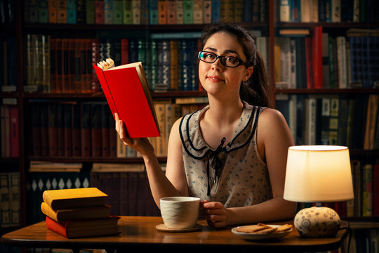 Quarantine.A young Caucasian woman with glasses is reading a book and holding a Cup of tea.The home library is in the background.The concept of self-isolation, distance learning and remote work