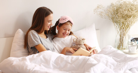 Happy woman and girl reading book on bed in morning