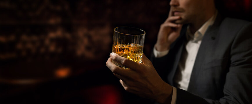 man wearing suit sits in the luxury bar in gentlemen club and drink whiskey. copy space