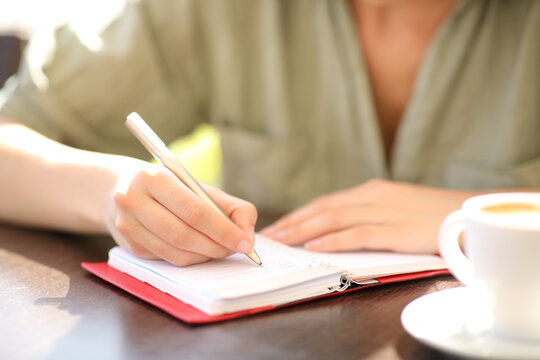 Woman hand writing on agenda in a coffee shop