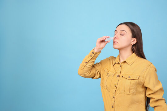 Woman using nasal spray on light blue background, space for text