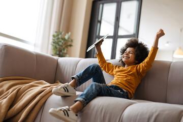 Obraz Black boy making fun and using tablet computer while sitting on sofa - fototapety do salonu
