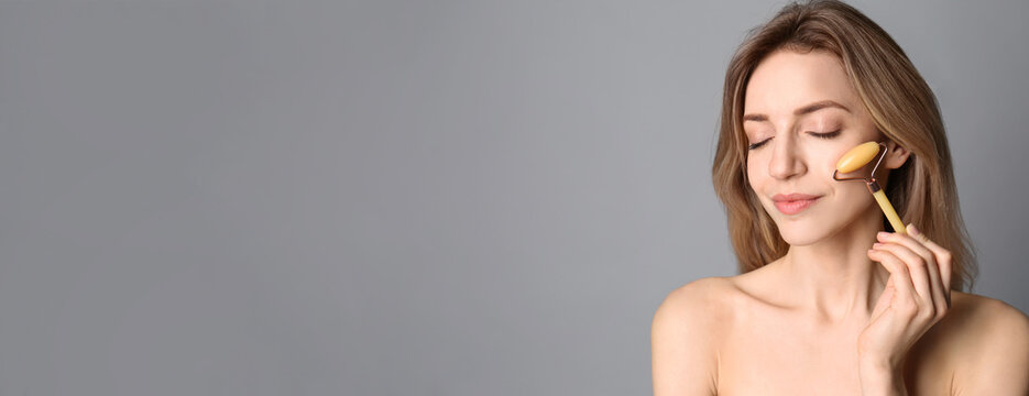 Young woman using natural jade face roller on light grey background, space for text. Banner design