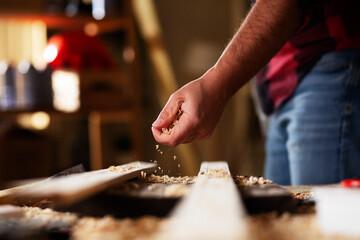 Fototapeta Young male carpenter working in workshop. Carpenter working on wood craft at workshop. obraz