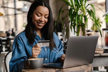Obraz Happy young african woman holding credit card - fototapety do salonu