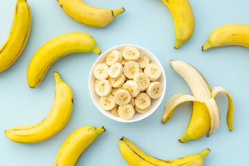 Many banana slices with whole bananas. Top view
