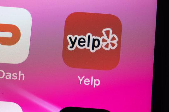 New York, USA - 26 April 2021: Yelp app logo on phone screen close-up top view, Illustrative Editorial.