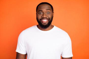 Photo of happy charming dark skin man smile good mood wear white t-shirt isolated on orange color...