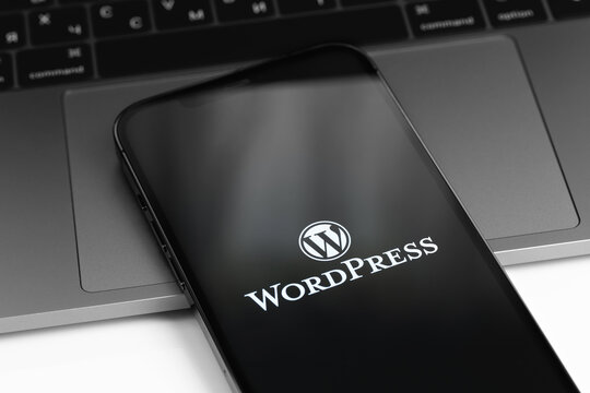 WordPress logo on screen smartphone, iPhone with notebook MacBook keyboard closeup. WordPress - open source site content management system. Moscow, Russia - April 11, 2021