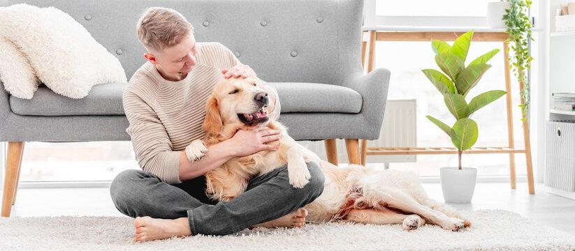 Man sitting with golden retriever dog