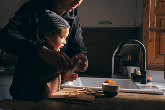 Unrecognizable man wiping hands of little son in kitchen