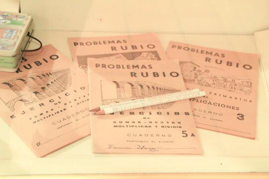 Old maths workbooks on a shelf