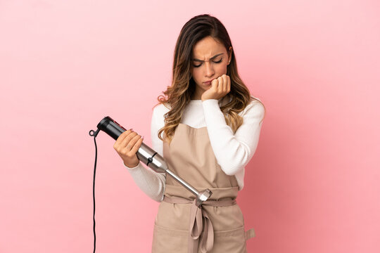 Young woman using hand blender over isolated pink background having doubts