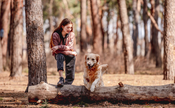 Girl with golden retriever dog in the wood
