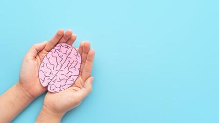 Woman hands holding human brain shape made from paper on light blue background. Awareness of Alzheimer, Parkinson's disease, dementia, stroke, seizure or mental health. Neurology and Psychology care. Wall mural