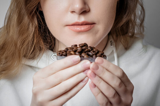 Loss of smell. Close up portrait of caucasian young woman sniffing coffee grains isolated on white background. Coronavirus concept