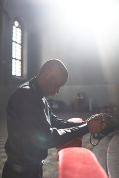 African catholic talking to God in his pray while standing in the church