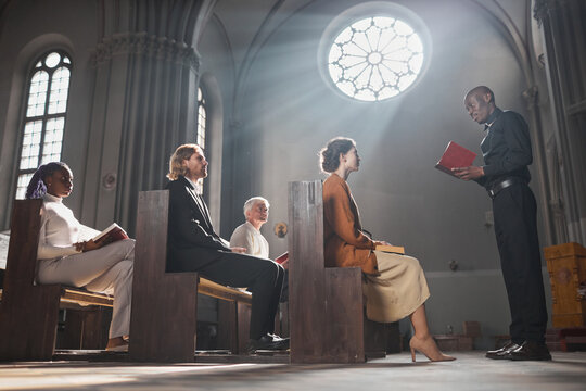 African young priest reading the Bible for faithful people while they sitting on the bench in the church