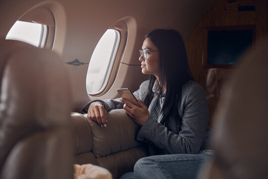 Happy smiling beautiful business woman in private jet