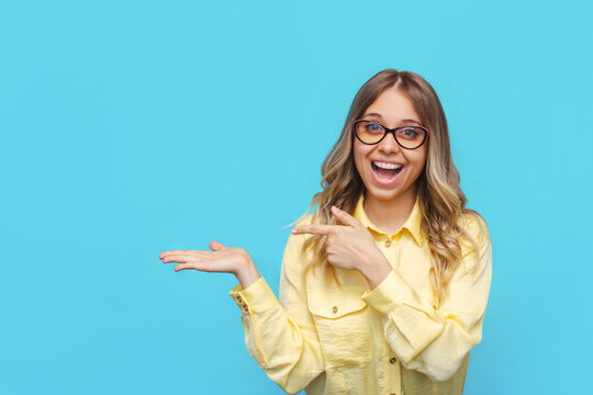 A young caucasian beautiful happy excited smiling blonde woman in a yellow shirt and glasses points with her index finger copyspace, hold hand demonstrating ads offer on a light color blue background
