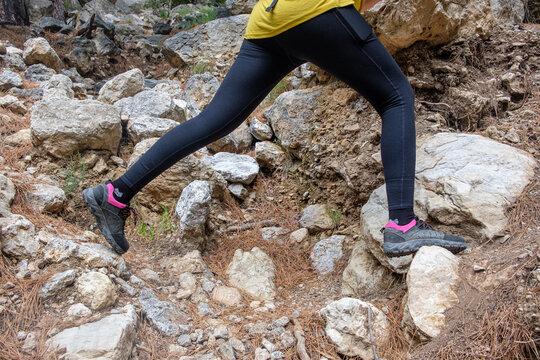 hiker is jumping between rocks at footpath