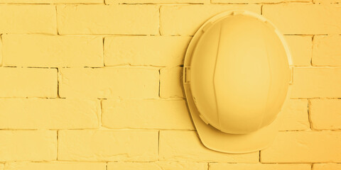 A yellow construction helmet hangs on a brick wall. Workplace health and safety concept.