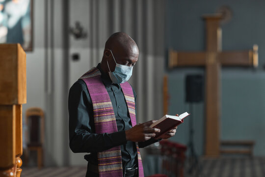 African priest in mask reading the Bible and holding the ceremony in the church