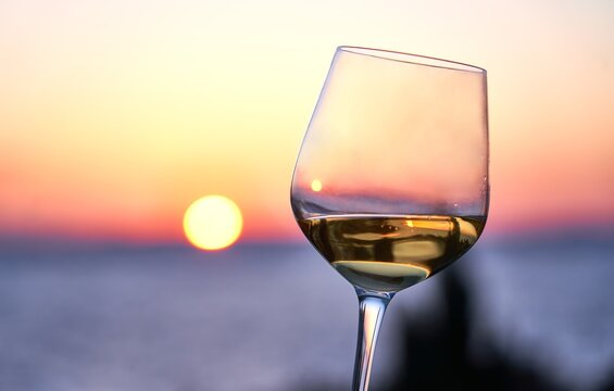 Close up image of glass of wine in woman's hand with the sea and sunset in the background. Summer holiday, vacation concept.
