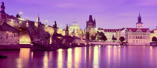 Romantic Charles Bridge in Prague, purple banner. Romantic Prague. Panoramic travel cityscape. Illuminated Charles Bridge reflected in Vltava river at night.