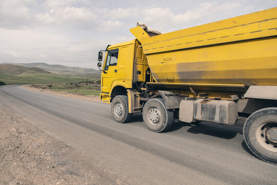big yellow dump truck on the highway