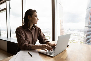 Dreamy young Caucasian businesswoman work on computer in modern office building look in distance making plans of career success or perspectives. Pensive female employee busy with laptop thinking.