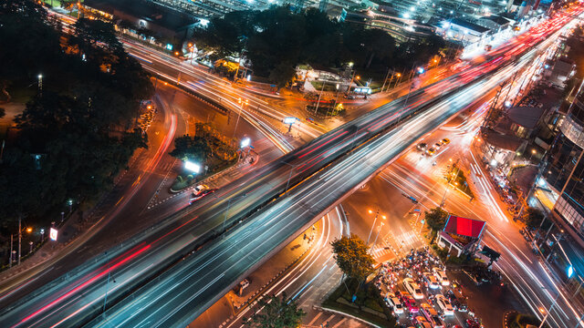 Car traffic transportation on road, bridge at junction intersection in Asia urban city, night cityscape high angle view, long exposure light trail. Asian city life, people transport lifestyle concept