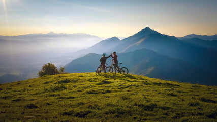 Fototapeta Two happy woman high five over the sunset after a successful mountain biking trip in the mountains. Celebrate a cross country cycling journey.