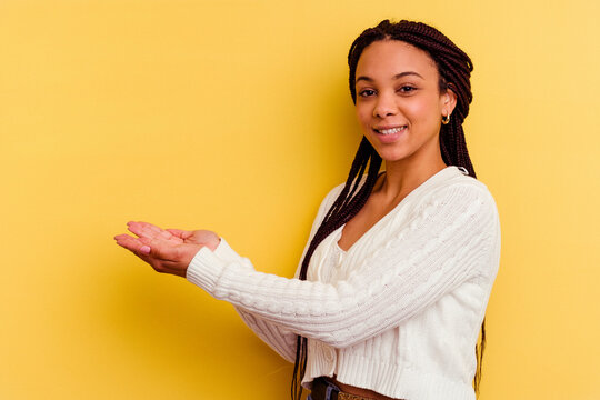 Young african american woman isolated on yellow background holding a copy space on a palm.