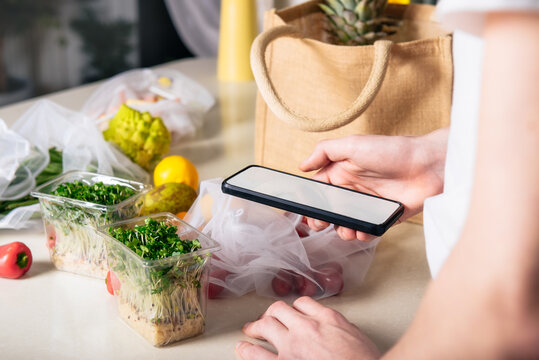 Online home food delivery of fresh vegetables and fruits. Young man holding phone and checking order list. Reusable bag with bio vegetables on white kitchen table. Local farmer healthy food.