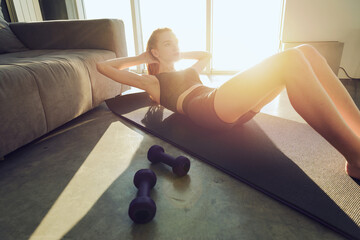 Young girl does gym exercises during sunrise. She is at home due to coronavirus codiv-19 quarantine
