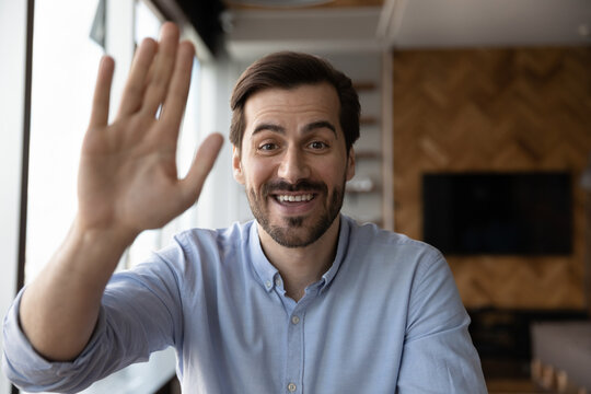 Headshot portrait of smiling young Caucasian man look at camera wave greet talk on video call online. Screen view of happy millennial male have webcam zoom digital conference. Virtual event concept.
