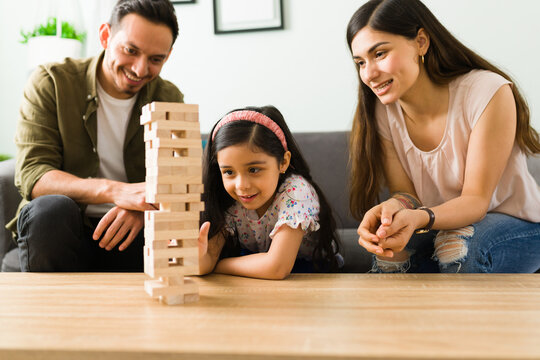 Cute kid trying to win the game with mom and dad