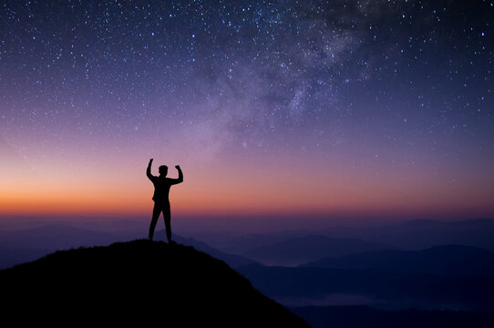 Young traveler standing and looking view star, Milky Way on top of mountain. He strong confidence and open arms under the night sky. He enjoyed traveling and was successful when he reached the summit.